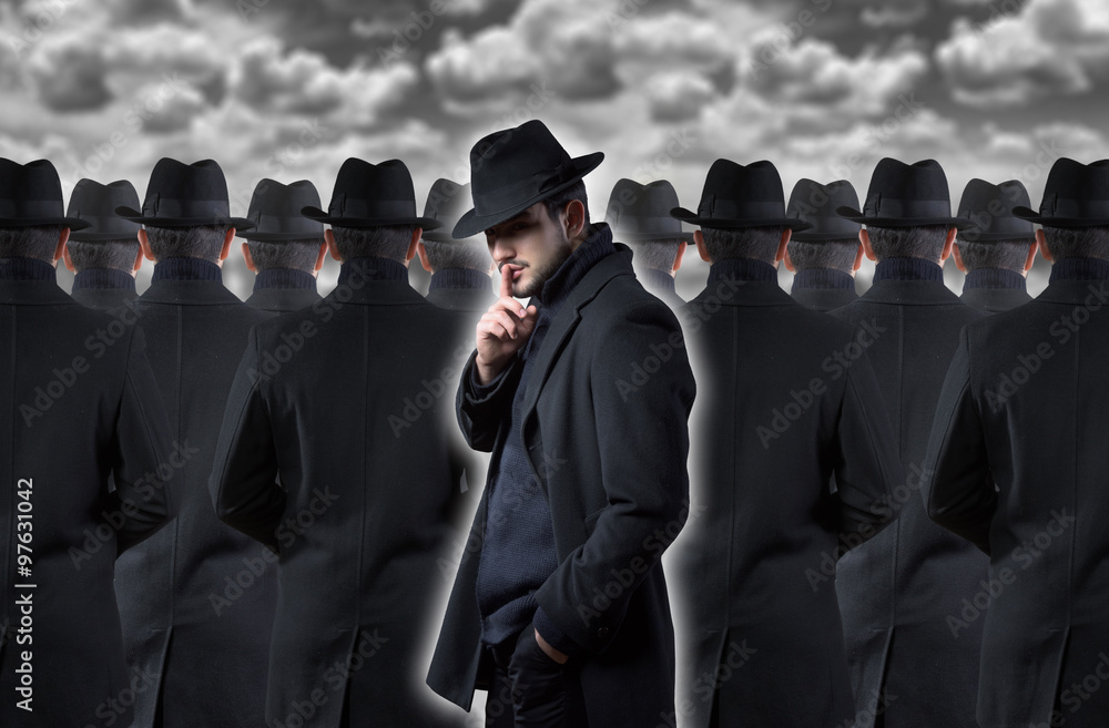 Fototapeta Mysterious man making a silence gesture while standing out from the crowd