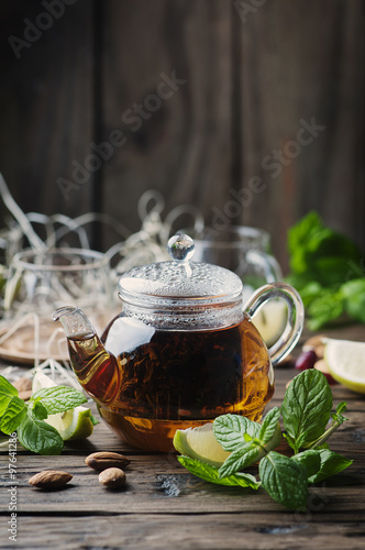Photo sur Toile The Hot black tea with lemon and mint on the wooden table
