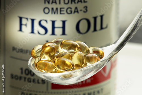 Fotografie, Obraz  Fish oil softgels in a spoon, bottle with capsules on the background