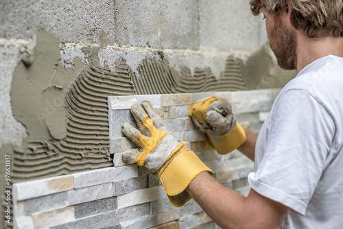 Fotografía  Hombre que presiona un mosaico ornamental en una cola en una pared