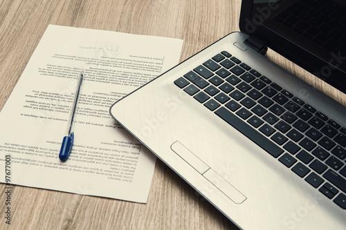 Canvas Print contratto firmato sul tavolo di un ufficio con un notebook di uomo di affari
