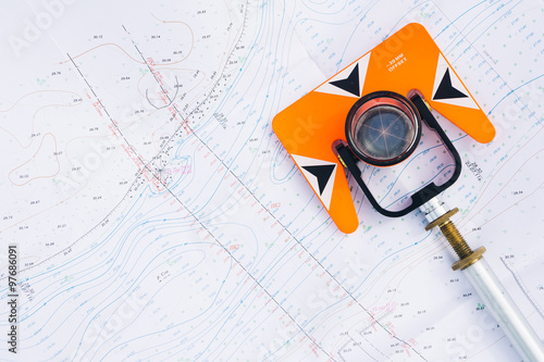 Photo  orange theodolite prism lies on a background geodetic maps of the area