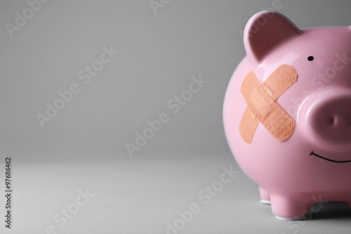 Piggy Bank with adhesive bandage on grey background Canvas Print