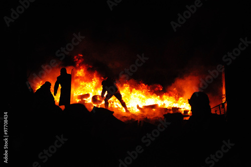 Fotografiet Protester refugee burn tires to stop the riot police