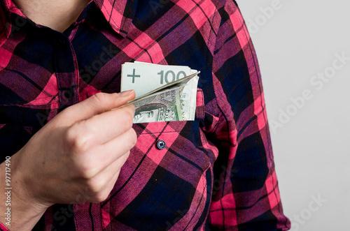Kobieta wyciąga polskie pieniądze z kieszeni - fototapety na wymiar