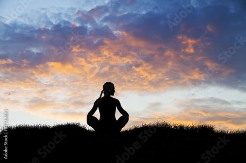 Foto op Plexiglas Ontspanning mujer meditando en el campo bajo las nubes del atardecer