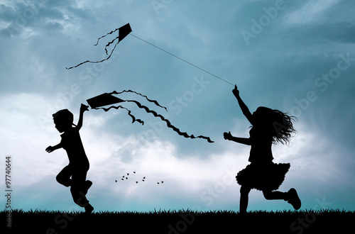Photo children with kite silhouette at sunset