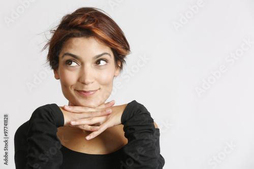 Bellissima ragazza con sguardo sbarazzino incroci le mani sotto il mento