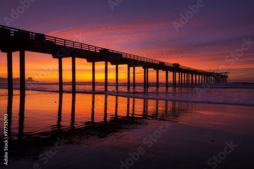 Silhouette pier at beach and brilliant sunset