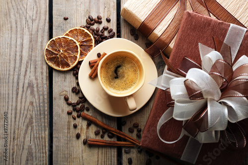 Poster de jardin Salle de cafe Beautiful gift, cup with coffee and coffee grains on wooden background