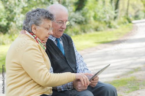 Fotografie, Obraz  Elderly couple sat on bench looking at tablet
