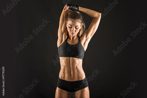 Fotografie, Obraz  Young sporty woman portrait doing stretching against black background