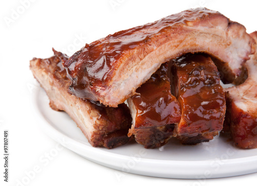 In de dag Grill / Barbecue Barbecued Ribs Close-up – A plate of pork spareribs with barbecue sauce. On a white plate and white background.