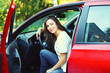 Beautiful smiling young woman driver behind the wheel red car
