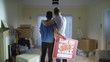 Happy affectionate young gay couple standing with 'sold' sign in new home