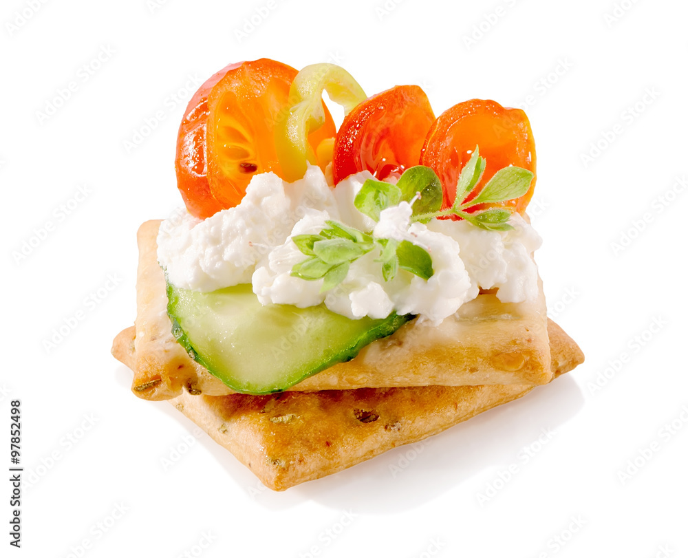 Fototapeta appetizer on crackers with cream cheese and vegetables close-up isolated on white background
