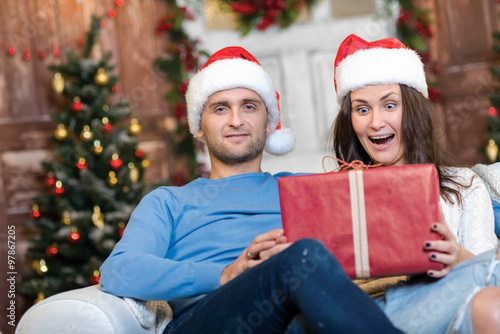 Fotografie, Tablou  Great Christmas surprise. Couple in love is sitting in festive C