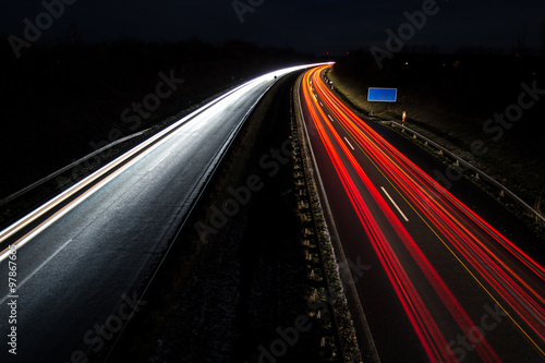 Car light trails with blue road sign, long exposure Fototapeta