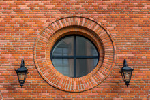 Beautifully Renovated Wall Of An Old Textile Factory With Round Window And Two Lanterns