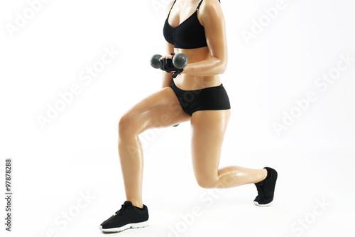 Obraz Umięśnione kobiece ciało, trening z hantlami. Kobieta w stroju sportowym podnosi ciężarki. - fototapety do salonu