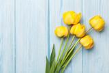 Fototapeta Tulipany - Yellow tulips over wooden table