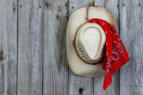 Fotografie, Obraz  Cowboy hat with bandanna hanging on rustic background