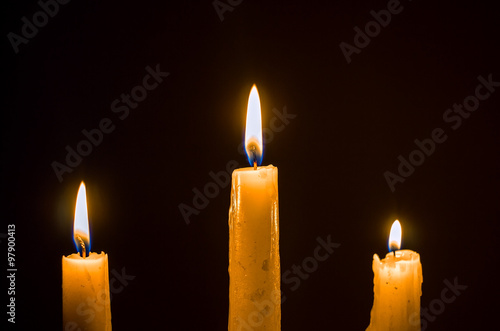 Fotografiet  Three burning wax candles on a black background, religion