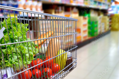 Fototapeta Shopping cart full of food in supermarket aisle side tilt obraz