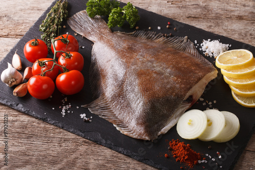 Tablou Canvas Fresh raw plaice with ingredients on a slate board. horizontal