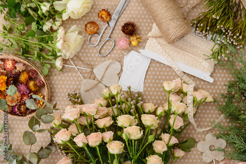Florist workplace: flowers and accessories on the table. Top vie
