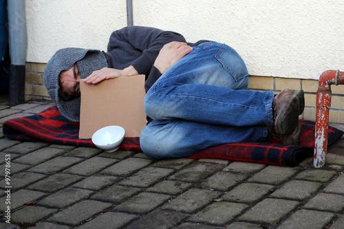 Fotografiet Bettler mit leerem Schild auf Straße liegend
