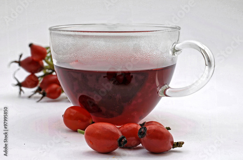 Fotografie, Obraz  rote Hagebuttentee  mit ganzen Fruechten