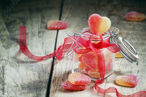 Foto op Aluminium Snoepjes Fruit jelly pink and yellow candy hearts in a glass jar with a p