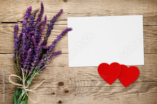 Fotografía  Salvia flowers and greeting card with two red hearts on wooden background