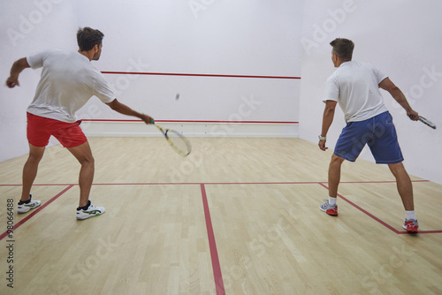 Fotografiet  Two best friends playing squash indoors