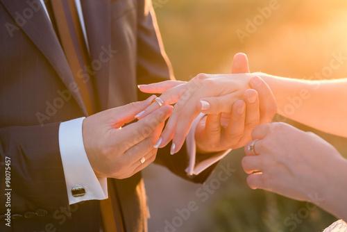 Fotografie, Obraz  Groom slipping ring on finger of bride at wedding