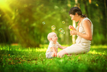 Happy Mother And Baby Blowing Bubbles In The Summer Park.