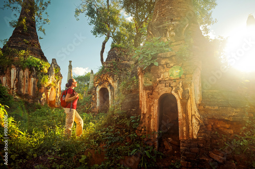 Canvas Print Backpacker traveling and looks at sunset among stupas. Myanmar