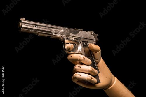 Fényképezés  A wooden hand brandishes a dummy gun