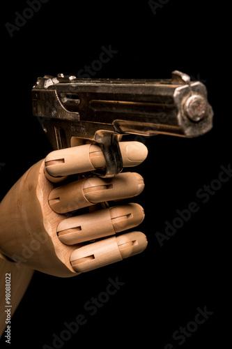 Fotografia, Obraz  A wooden hand brandishes a dummy gun
