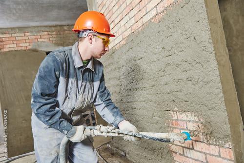 Plasterer spraying plaster on wall
