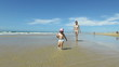 tender funny family scene of two years age blonde baby with blue swimwear with brown hair woman mother white bikini dancing, running and playing in sand beach seaside ocean and sky