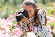 Female Taking Photo Of  Flowering Roses