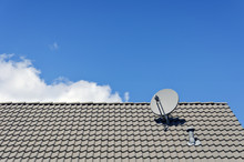 Satellite Dish On Tiled Roof Of A House
