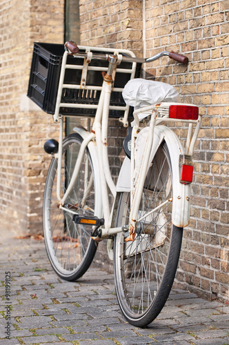 Photo  White transport bike with a crate parked against an ancient brick wall, Amsterdam, The Netherlands