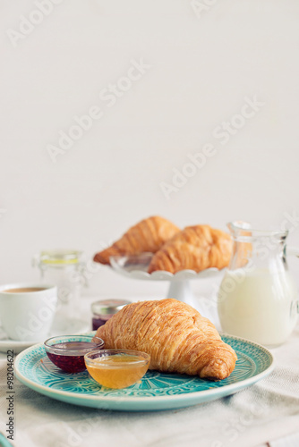 Fotografie, Tablou  Romantic breakfast with croissant, coffee, milk, honey and jam on the table