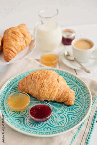 Romantic breakfast with croissant, coffee, milk, honey and jam on the table Tablou Canvas