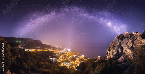Poster Chocoladebruin Beautiful night landscape with Milky Way against city lights