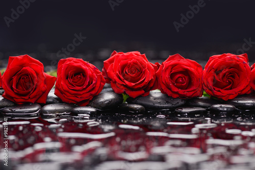 Photo sur Toile Spa Still life with row of red rose and wet stones