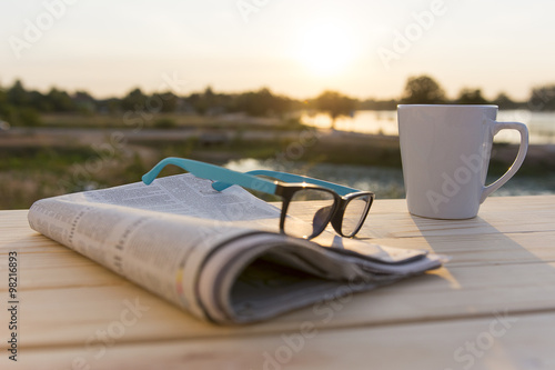 Close up glasses with newspaper and Coffee on the table in the morning selective focus #98216893